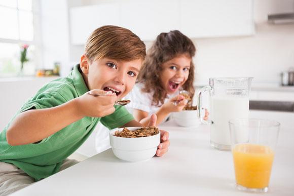 Um casal de crianças faz um lanche com cereais sem açúcar, leite e sucos naturais: uma boa opção - Crédito: wavebreakmedia/Shutterstock