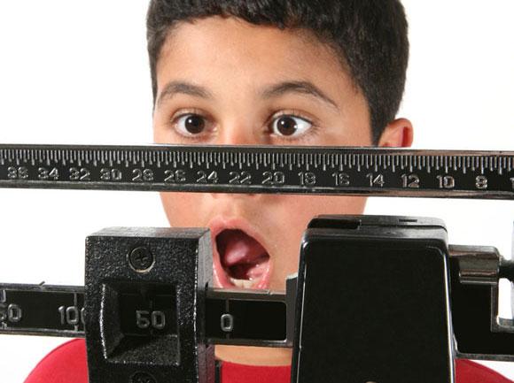Menino se assusta com o seu próprio peso: esse excesso é fator de risco obesidade na fase adulta –Crédito: Stephen Coburn/Shutterstock